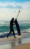 Kitesurf. kitesurfer con kiteboard caminando en la playa — Foto de Stock