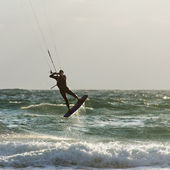 Kitesurfing. Kitesurfer rides the waves at sunset — Stock Photo