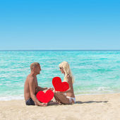 Loving couple at sandy sea beach with red hearts — ストック写真