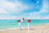 Loving couple at sandy sea beach with red hearts — Stock Photo