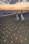 Couple at sea beach in candles against sunset — Stockfoto