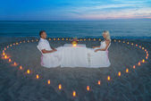 Couple at beach romantic dinner with candles heart — Stock Photo