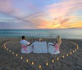 Young couple during romantic dinner with heart of candlelights o — Stock Photo