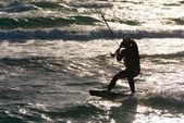 Kitesurf. kitesurfer cavalga as ondas ao pôr do sol — Fotografia Stock