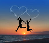 Loving couple flying in sky against sea — Стоковое фото