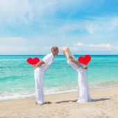 Loving couple at sandy sea beach with red hearts — Stockfoto