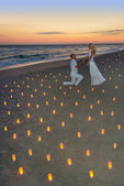Couple at sea beach in candles against sunset — Stock Photo