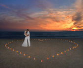 Young couple in candles heart at sea beach against sunset — Stock fotografie