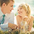 The bride and groom lie on the grass — Stock Photo