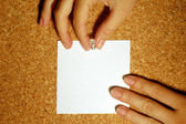 Hands put a blank paper on the cork board — Stock Photo