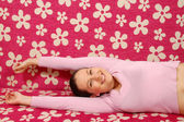 Smiling woman is lying on pink couch — Stock Photo