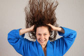 Smiling woman in bathrobe with flying wet hair — Stock fotografie