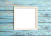 White Vintage picture frame on blue wood background — Stock Photo