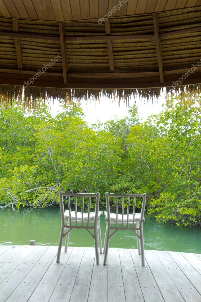 Two white wooden canvas chair on private terrace of the mangrove forest water — Stock Photo #12308015