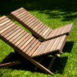 Stock Photo: Wooden lawn chairs in the spring garden.