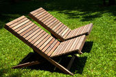 Wooden lawn chairs in the spring garden. — Stock Photo