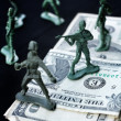 Stock Photo: Toy soldier standing with dollar