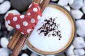 Red fabric heart with hot cappuccino — Stock Photo