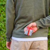 Man hide gift box behind his back — Stock Photo