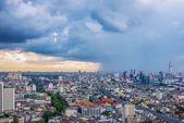 Big city with rain cloud falling — Stock Photo