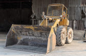 Old yellow tractor parks in factory — Stock Photo