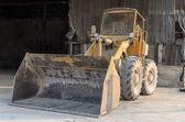 Parques de amarelo trator velho na fábrica — Foto Stock