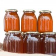 Glass jars with honey on a table isolated - Stock Photo
