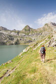 Woman walking in the spanish pyrenees by Estanes lake during sun — Stock Photo