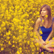 Fashion young woman sitting on a yellow spring Field. — Stock Photo