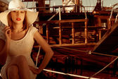 Elegant Lady wear hat and lace dress , sitting near the wooden yachts . — Stock Photo