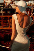 Back side view of lady with a hat and lace dress near the wooden yachts — Stock Photo