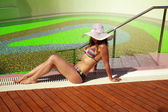 Sexy woman in bikini and hat sunbathing at pool resort — Stock Photo