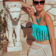 Fashion shot of young female in summer outfits near a statue — Stock Photo
