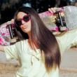 Fashion portrait of attractive girl with skateboard . shot in nature — Stock Photo #27375645