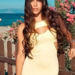 Beautiful brunette in yellow elegant dress — Stock Photo #29188253