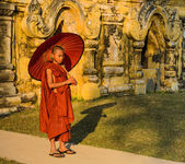 Burmese Buddhist novice holding an umbrella — Stock Photo