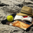 Stock Photo: On cliff book, hat and apple