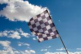 Checkered flag against the blue sky — Foto Stock