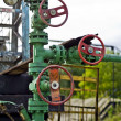 Stock Photo: Pump jack and oil well