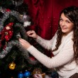 Girl with gifts near a Christmas tree — Stock Photo #16298093