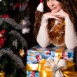 Girl with gifts near a Christmas tree — Stockfoto #16298205