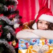 Girl with gifts near a Christmas tree — Stockfoto #16298235