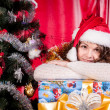 Girl with gifts near a Christmas tree — ストック写真 #16298235