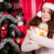 Girl with gifts near a Christmas tree — Foto Stock