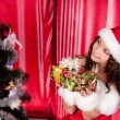 Girl with gifts near a Christmas tree — Stock Photo #16298327