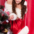 Girl with gifts near a Christmas tree — Stockfoto #16298477
