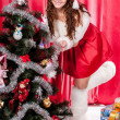 Foto Stock: Girl with gifts near a Christmas tree