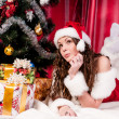 Girl with gifts near a Christmas tree — Stock Photo #16298633