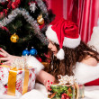 Girl with gifts near a Christmas tree — Stockfoto #16298663
