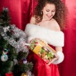 Girl with gifts near a Christmas tree — ストック写真